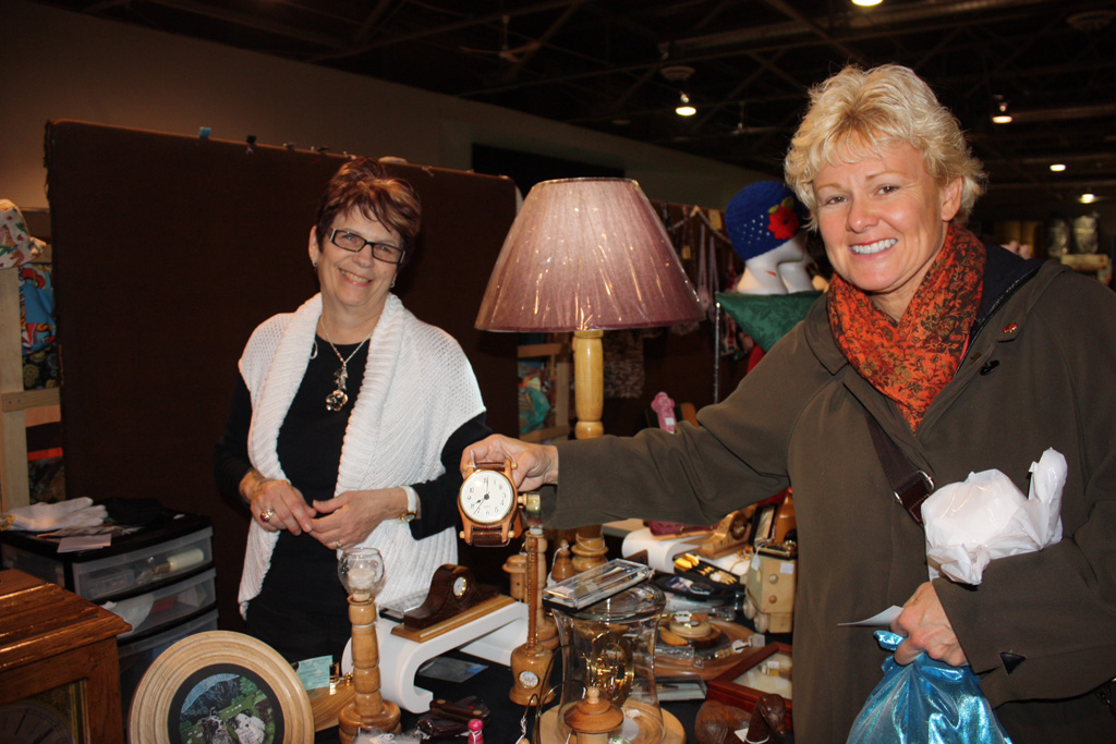 Cathy Bartlett mans Basil Etmanski's display of wooden crafts at the Christmas Craft sale in Renfrew.