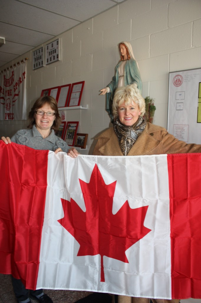 Anne Lepine, principal of St, Mary School in Wilno, is pleased to receive a flag